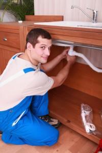 a plumber setting a flexible pipe below a tap
