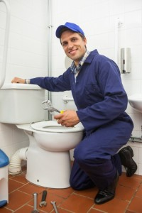 Good looking plumber repairing toilet in public bathroom