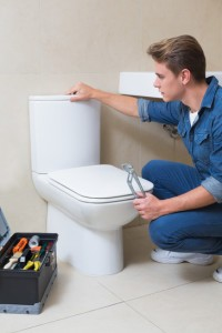 Side view of a handsome plumber with toolbox doing toilet reparation