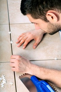 Young man laying tiles on the floor